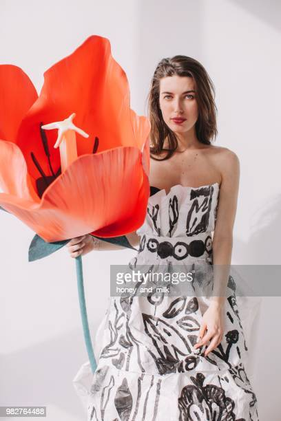 woman wearing a paper dress holding an artificial tulip - strapless evening gown stock pictures, royalty-free photos & images