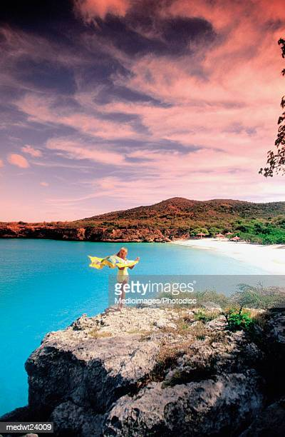 Woman wearing a pareu and standing on the cliffs of Knip Beach, Curacao, Caribbean