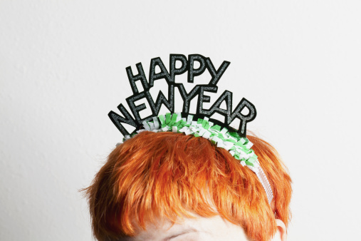 A woman wearing a party tiara with Happy New Year on it, top of head - gettyimageskorea