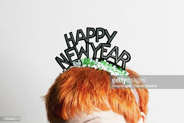 a woman wearing a party tiara with happy new year on it, top of head - dia de ano novo imagens e fotografias de stock