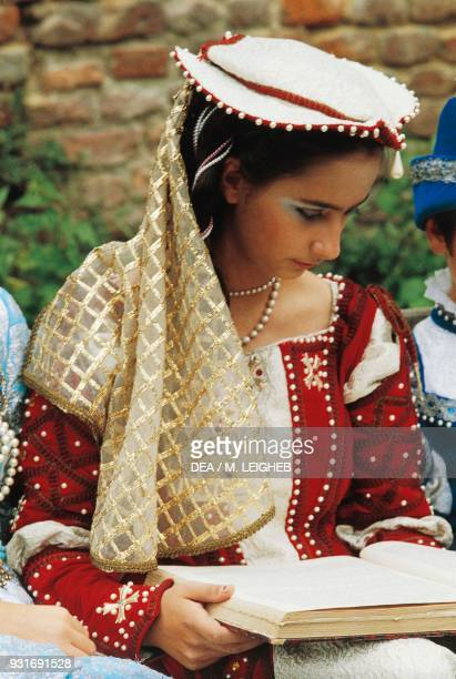 Woman wearing a period costume reading a book Palio di Asti Piedmont Italy
