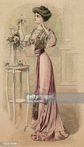 Woman wearing a pink Crepe de Chine dinner dress with Liberty satin decorations lace corset with wide sleeves creation by Drecoll colored engraving...