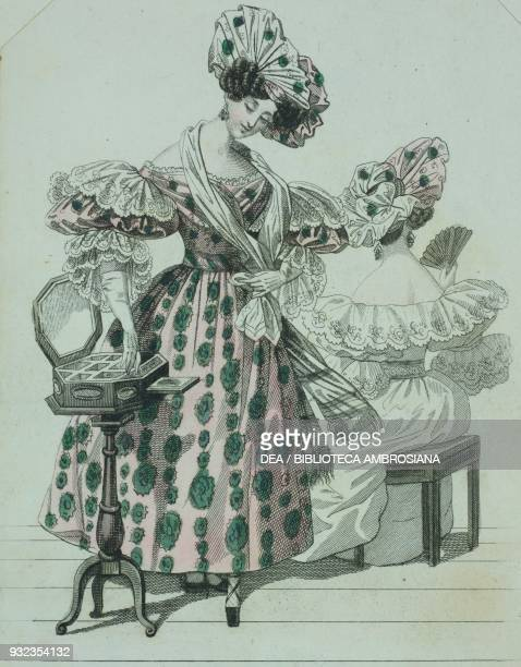 Woman wearing a pink dress with green Greekpattern shortpuffed sleeves gloves adorned with lace and a matching white and pink hat a woman wearing a...