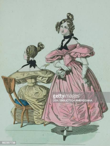 Woman wearing a pink dress with shortpuffed sleeves white gloves and blackribboned bow around her neck and hair styled high on her head and a woman...