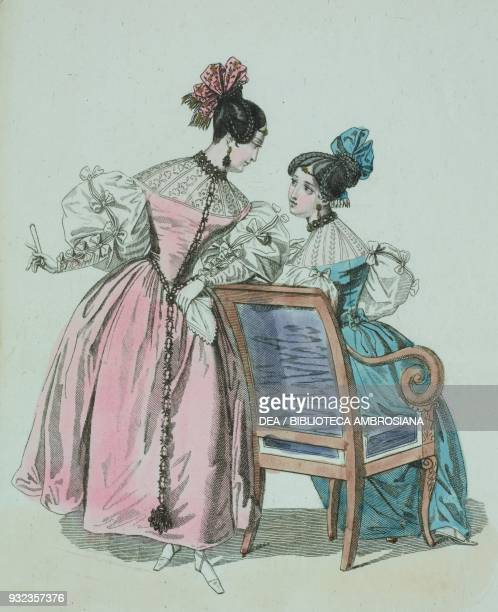 Woman wearing a pink dress with whitepuffed sleeves fastened with bows with a pink bow in her hair woman wearing the same dress in blue with blue bow...