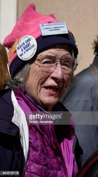 A woman wearing a pink 'pussy hat' adorned with buttons supporting the American Civil Liberties Union universal health care and other Progressive...