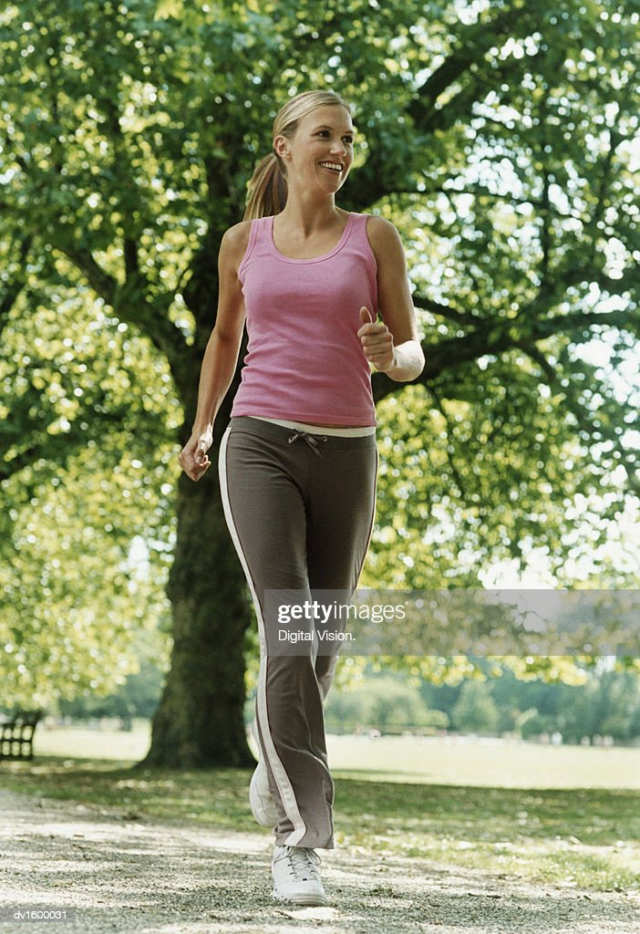 Woman Wearing a Pink Vest Jogging Through a Park : Stock Photo