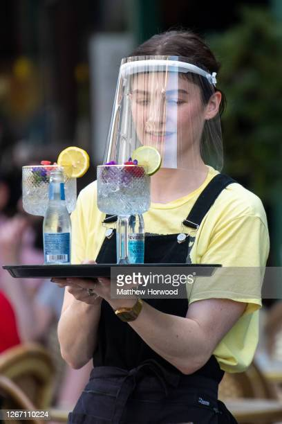 Woman wearing a plastic face visor serves drinks outdoors at Gin and Juice gin bar on August 12, 2020 in Cardiff, Wales. Coronavirus lockdown...