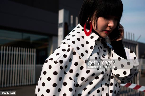 TOPSHOT A woman wearing a polkadot jacket phones prior to the women's Fall/Winter 2018/2019 collection fashion show by Gucci in Milan on February 21...