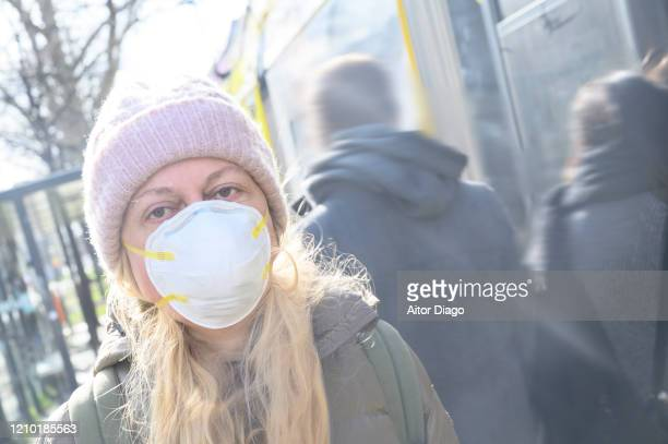 woman wearing a protection mask near the tram station. unrecognizable people pass behind it. berlin, germany. - 1918 flu pandemic stock pictures, royalty-free photos & images