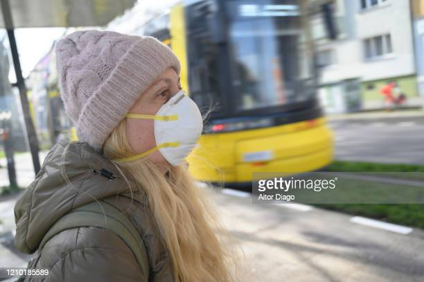 woman wearing a protection mask waiting for the tram which is just coming. berlin, germany. - 1918 flu pandemic stock pictures, royalty-free photos & images