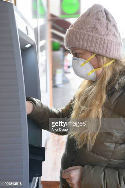 woman wearing a protection mask withdrawing money from an atm in the street. berlin, germany. - viral infection stock pictures, royalty-free photos & images