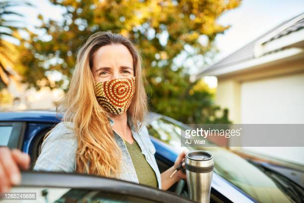 a woman wearing a protective fabric mask and smiling at the camera - one mature woman only stock pictures, royalty-free photos & images