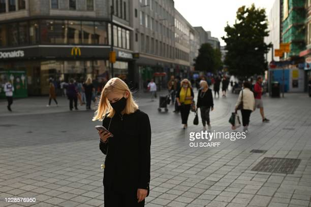 Woman wearing a protective face covering, checks her phone as she walks through Liverpool city centre, north-west England on September 18, 2020 after...
