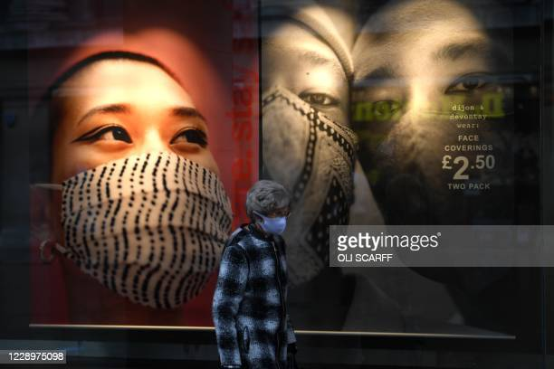 Woman wearing a protective face covering passes a shop window display in central Nottingham in central England on October 9, 2020. - Pubs and...