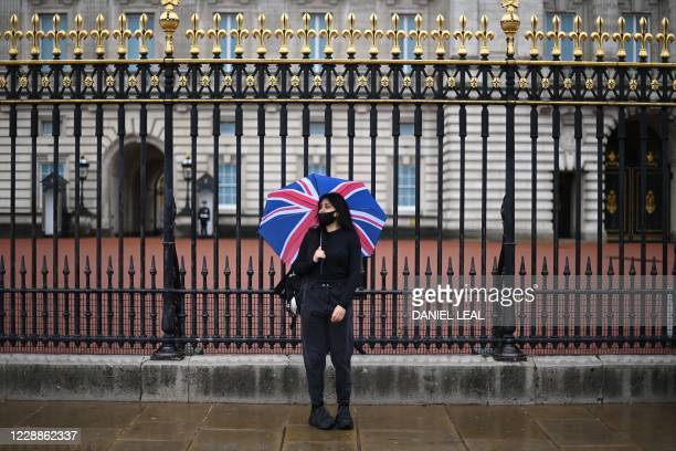Woman wearing a protective face covering, shelters from the rain under a Union flag umbrella outside Buckingham Palace in central London on October...
