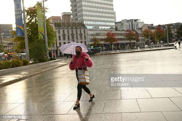 Woman wearing a protective face covering shelters from the rain under an umbrella in central Nottingham in central England on October 9, 2020. - Pubs...
