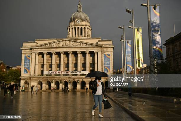 Woman wearing a protective face covering shelters from the rain under an umbrella as she walks past the Town Hall in central Nottingham in central...