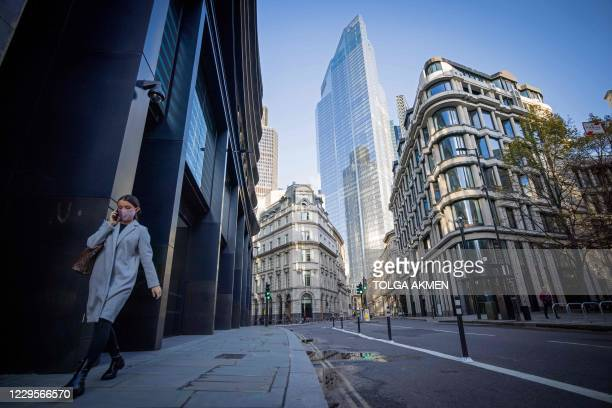 Woman wearing a protective face covering to combat the coronavirus walks along a quiet street in the City of London on November 10, 2020. - Britain's...