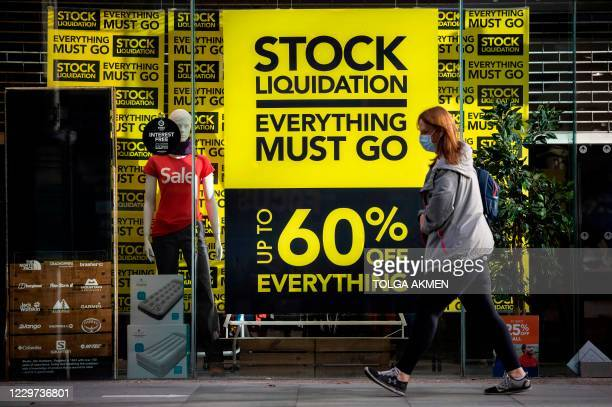 Woman wearing a protective face covering to combat the spread of the coronavirus, walks pas a shop advertising a closing-down sale in central London,...