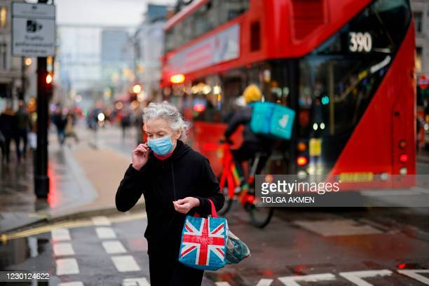 Woman wearing a protective face covering to combat the spread of the coronavirus, crosses Oxford Street in central London on December 14 as it is...