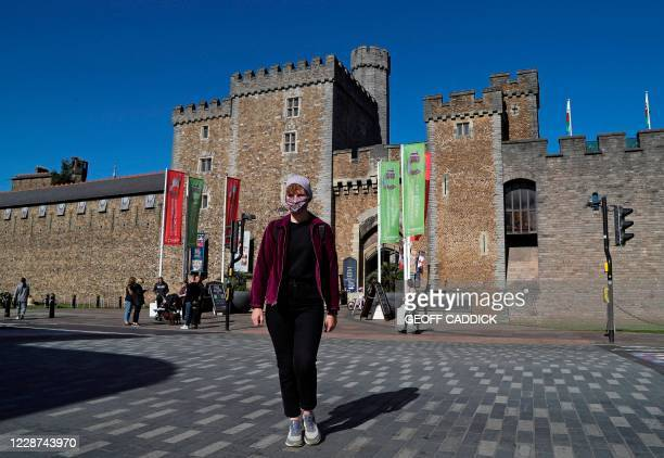 Woman wearing a protective face covering, walks past the castle walls in the late summer sunshine in Cardiff, south Wales on September 27 during...