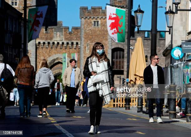 Woman wearing a protective face covering, walks through the city in the late summer sunshine in Cardiff, south Wales on September 27 during...