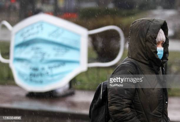 Woman wearing a protective face mask amid the COVID-19 coronavirus epidemic walks next to an art-object of the largest medical mask in Ukraine during...