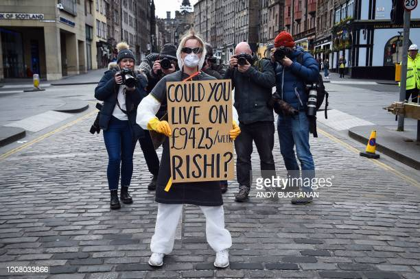 Woman wearing a protective face mask and gloves holds a placard complaining about the lack of suport for the self-employed and zero hours contract...