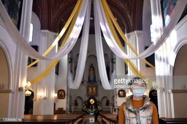 A woman wearing a protective face mask attends a traditional blessing cakes and eggs on the eve of Catholic Easter in Minsk on April 11 2020 during...