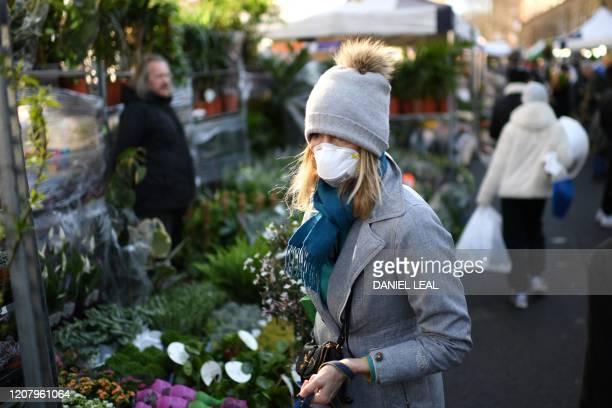Woman wearing a protective face mask browses in Columbia Road flower market in east London on Mother's Day, March 22, 2020. - Up to 1.5 million...