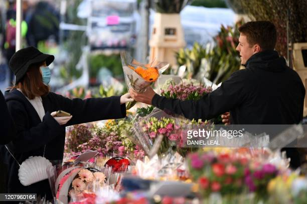 A woman wearing a protective face mask buys a bunch of flowers from a stall in Columbia Road flower market in east London on Mother's Day March 22...
