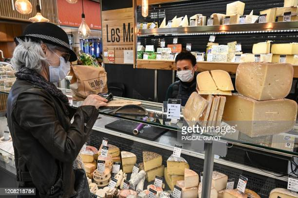 Woman wearing a protective face mask buys cheese at a store in the center of Montpellier, south of France, on March 25 on the ninth day of a strict...