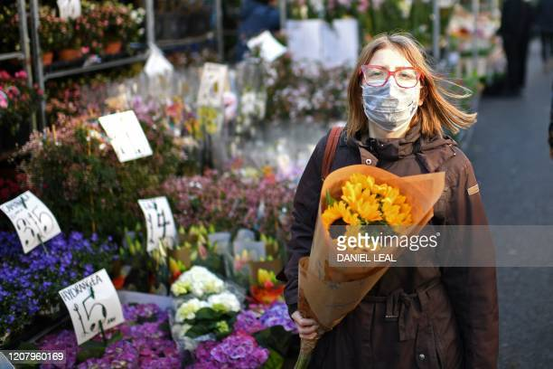 A woman wearing a protective face mask carries a bunch of flowers during a visit to the Columbia Road flower market in east London on Mother's Day...