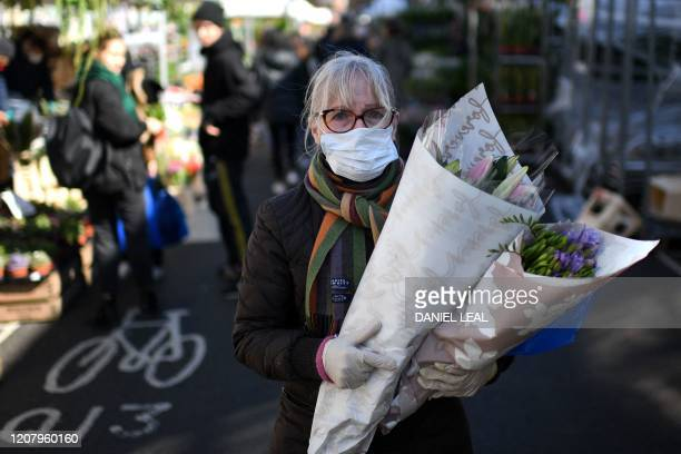 A woman wearing a protective face mask carries flowers after a visit to Columbia Road flower market in east London on Mother's Day March 22 2020 Up...