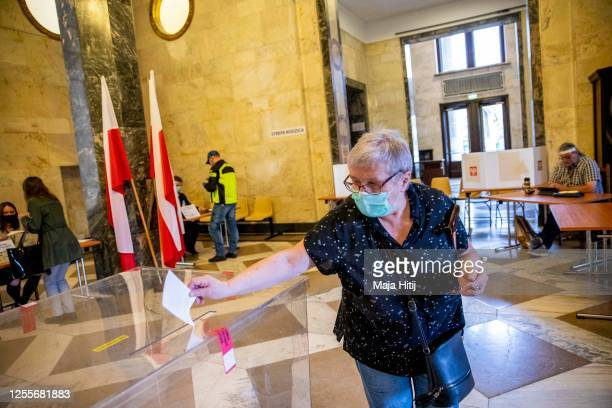 A woman wearing a protective face mask casts her ballot during Poland's Presidential election runoff on July 12 2020 in Warsaw Poland The latest...