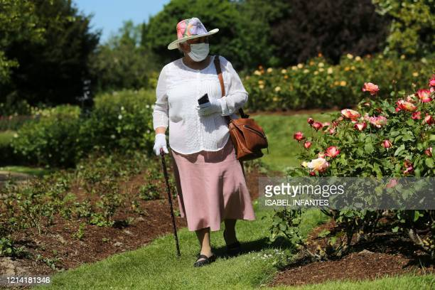 Woman wearing a protective face mask enjoys the sunshine in Queen Mary's Rose Gardens in Regent's Park in London on May 20 as temperatures in the...