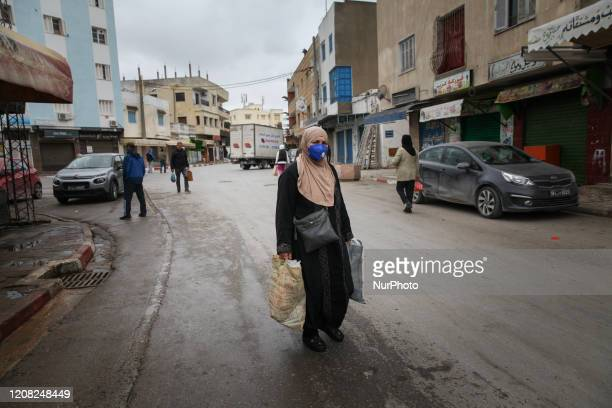 Woman wearing a protective face mask, holds bags of food as she walks in the street outside the municipal market of Ariana downtown, northern...