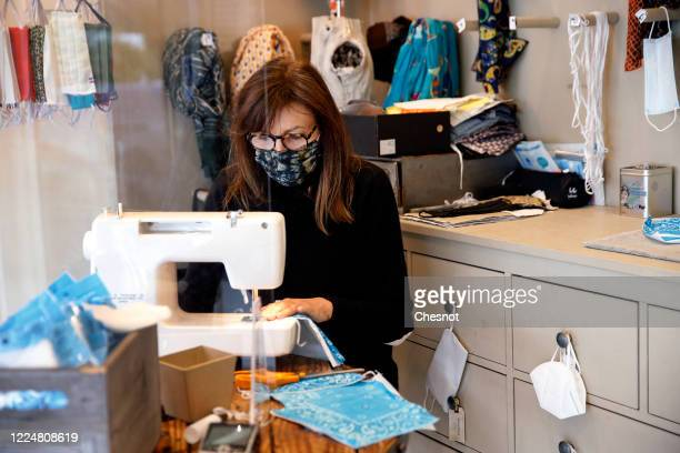 Woman wearing a protective face mask makes a protective face mask with a sewing machine in a fashion store as France is slowly reopening after almost...