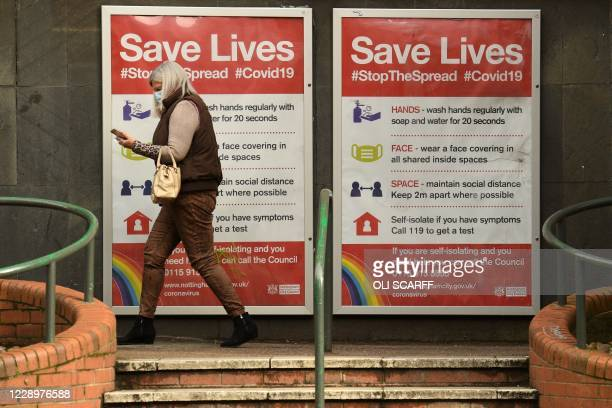 Woman wearing a protective face mask passes boards displaying information how to restrict the spread of coronavirus covid-19, in central Nottingham...