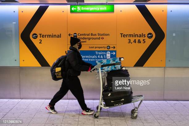 A woman wearing a protective face mask prepares to board a flight at Heathrow Airport on March 16 2020 in London England As the coronavirus pandemic...
