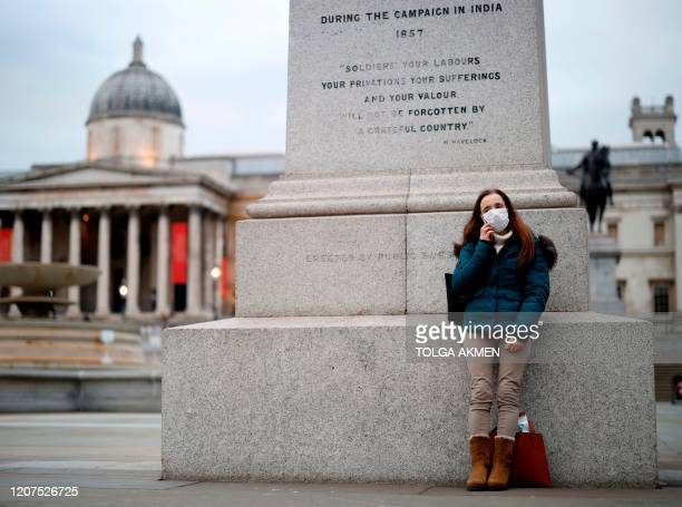A woman wearing a protective face mask rests in Trafalgar Square in central London on March 17 2020 Britain on Tuesday ramped up its response to the...