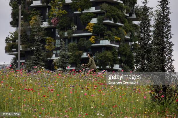 A woman wearing a protective face mask rides a bicycle past a field of blooming flowers at 'BAM Biblioteca degli Alberi di Milano' park on May 06...