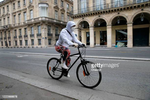 A woman wearing a protective face mask rides her bicycle in the deserted and carfree rue de Rivoli as the lockdown continues due to the epidemic of...