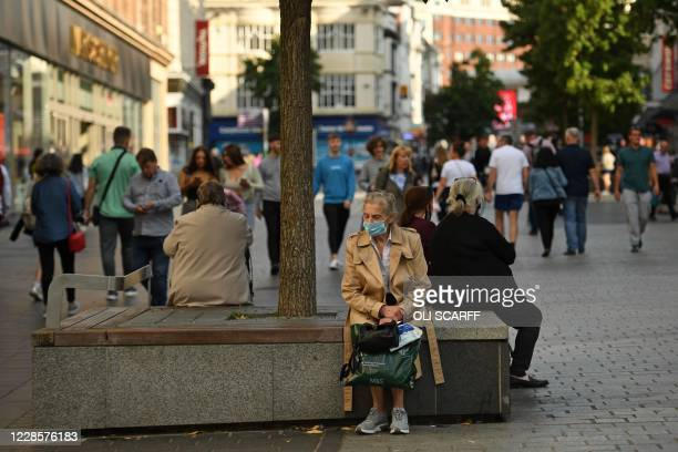 Woman wearing a protective face mask sits in Liverpool city centre, north-west England on September 18, 2020 after the British government imposed...