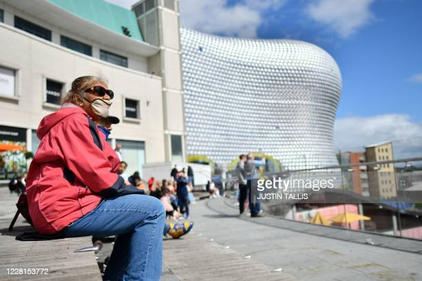 Woman wearing a protective face mask sits outside the Bullring shopping centre in Birmingham, central England on August 22 as Britain's second-city,...