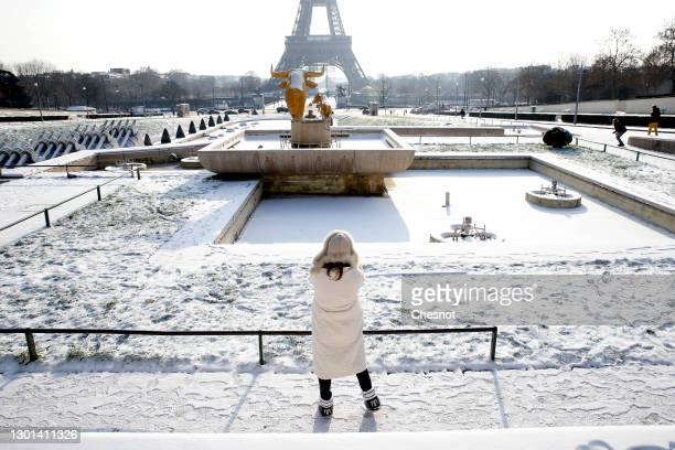 Woman wearing a protective face mask takes a picture of the Eiffel Tower in the gardens of Trocadero covered in snow following a light overnight...