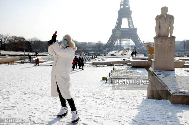 Woman wearing a protective face mask takes a selfie with the Eiffel Tower in the gardens of Trocadero covered in snow following a light overnight...