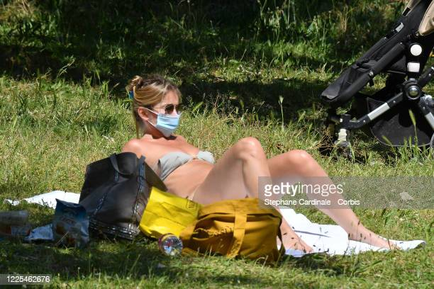 A woman wearing a protective face mask takes sunbathing in the Bois de Boulogne after France eased lockdown measures taken to curb the spread of the...