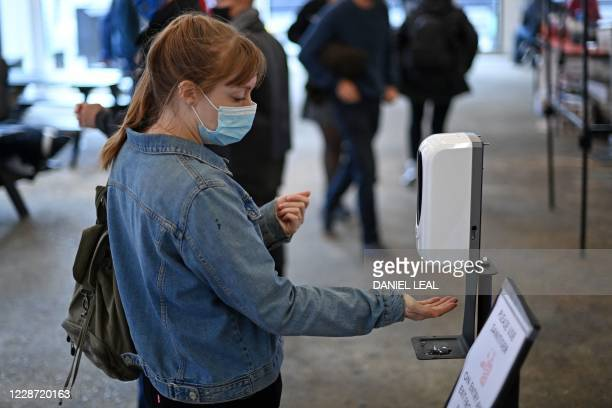 Woman wearing a protective face mask uses a hand sanitiser in The Old Truman Brewery's markets in east London on September 26 as Londoners live with...